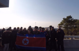 Our tourgroup holding a North Korean flag at the DMZ